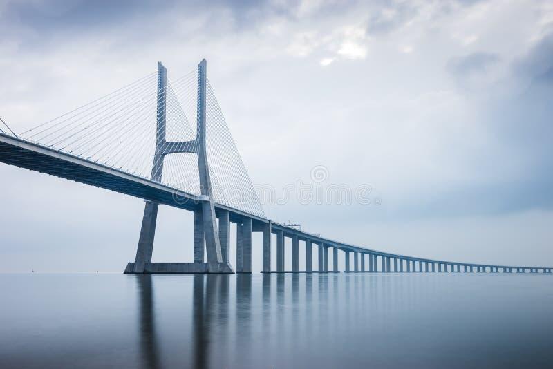 Vasco da Gama Bridge på soluppgång i Lissabon, Portugal honom länge royaltyfri bild