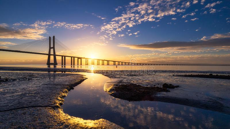 Vasco da Gama bridge at sunrise in Lisbon, Portugal. Vasco da Gama Bridge is a cable-stayed bridge flanked by viaducts and. Rangeviews that spans the Tagus stock photography