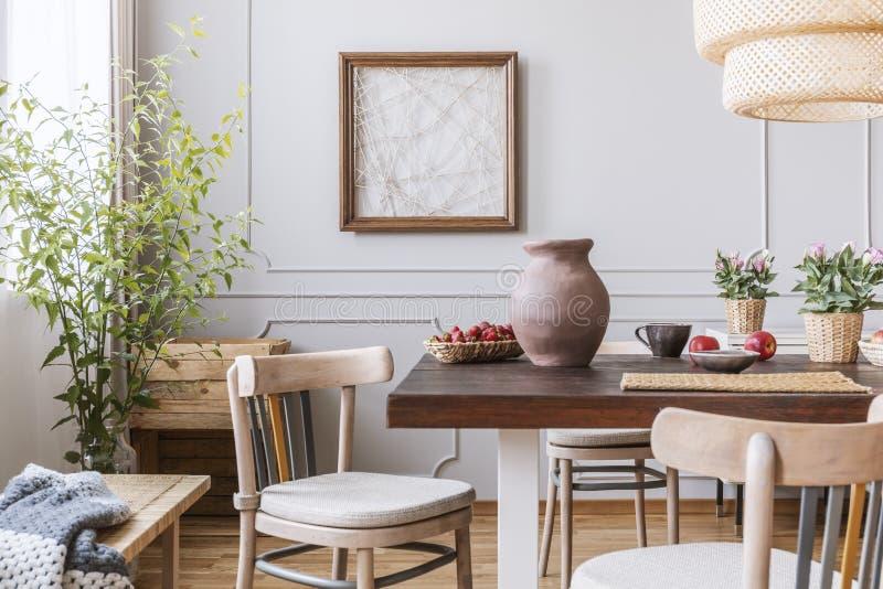 Vase à argile sur la table dans un intérieur de salle à manger avec une usine, des chaises et l'art sur un mur photos libres de droits