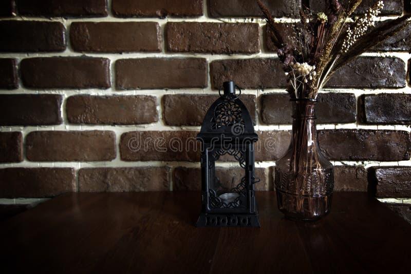 Vase à fleur d'annonce de lampe de lanterne de vintage sur la table avec le CCB de mur de briques photo libre de droits
