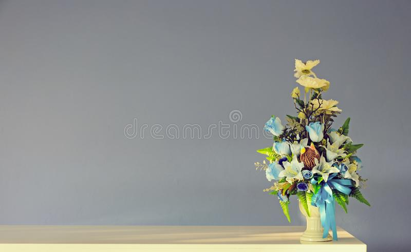 Vase à fleurs artificielles de bouquet sur la table ene ivoire avec le mur gris f photographie stock