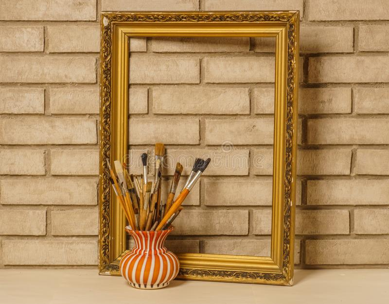 Vase with artistic brushes and the frame on the background of old white brick wall stock photos