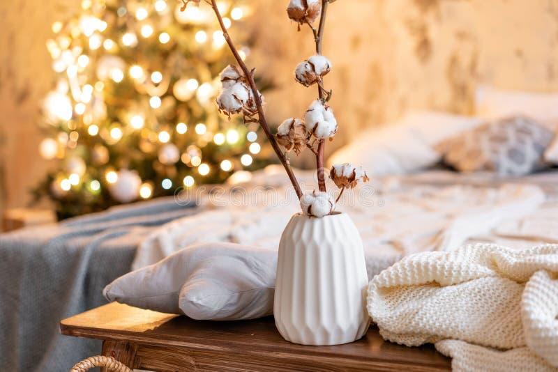 Vase avec des branches de coton Appartements de style de grenier, arbre de Noël Lit dans la chambre à coucher, grand Windows élev photos libres de droits