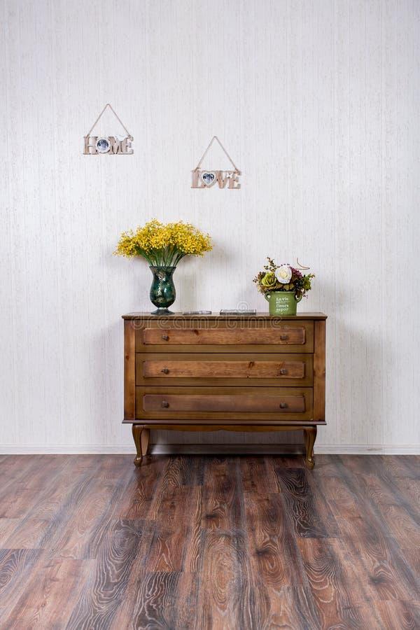 Vase avec des flovers sur la raboteuse dans l'inrerrior à la maison photographie stock