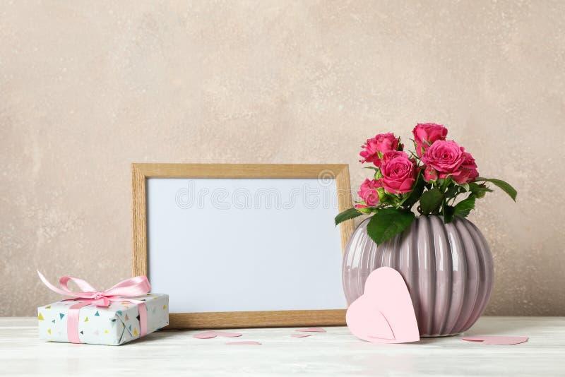 Vase avec les roses roses, le cadre vide, le cadeau et peu de coeurs sur la table blanche image libre de droits
