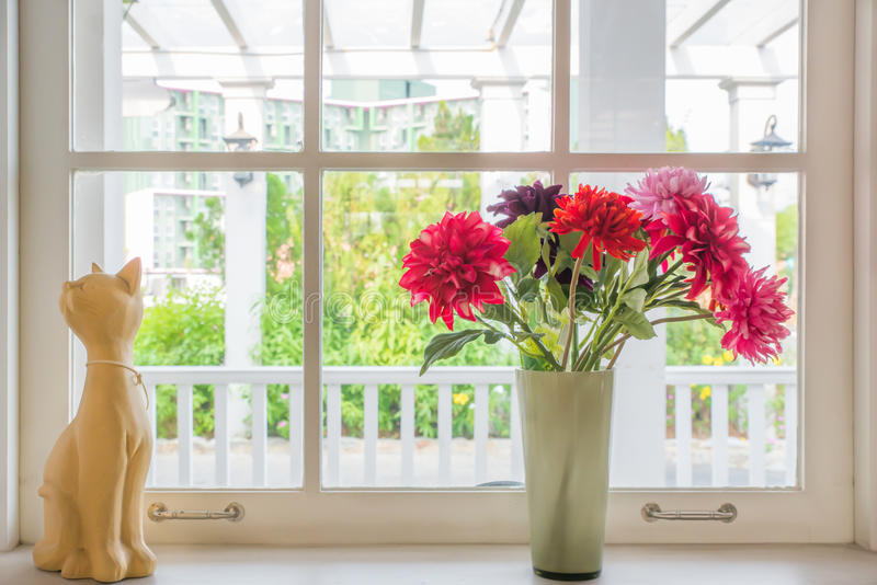 Vase avec une poupée de fleur et de chat sur la maison de campagne de rebord de fenêtre image libre de droits