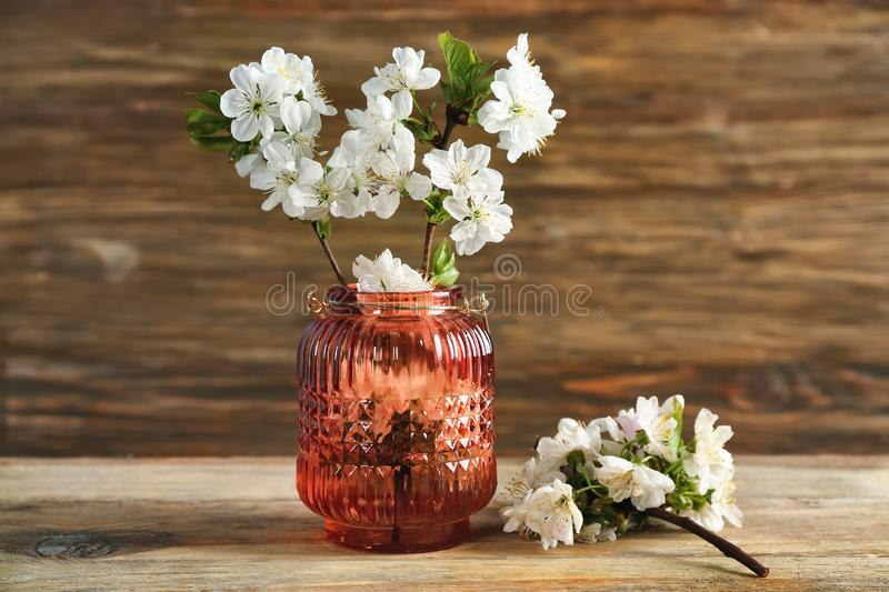Vase with beautiful blossoming branches on wooden table stock images
