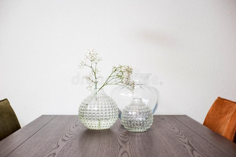Vase with beautiful flowers on diner table, modern design luxury. White wall royalty free stock photo