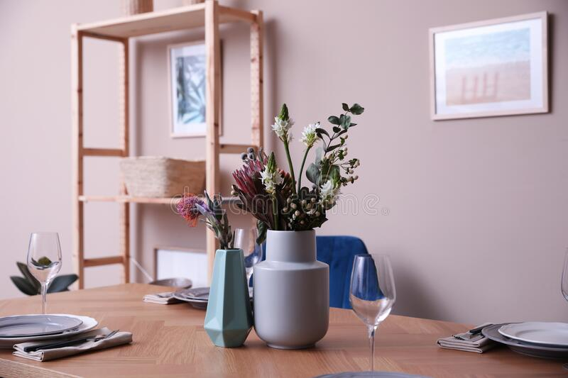 Vase with beautiful flowers on wooden table indoors. Element of modern interior stock photo