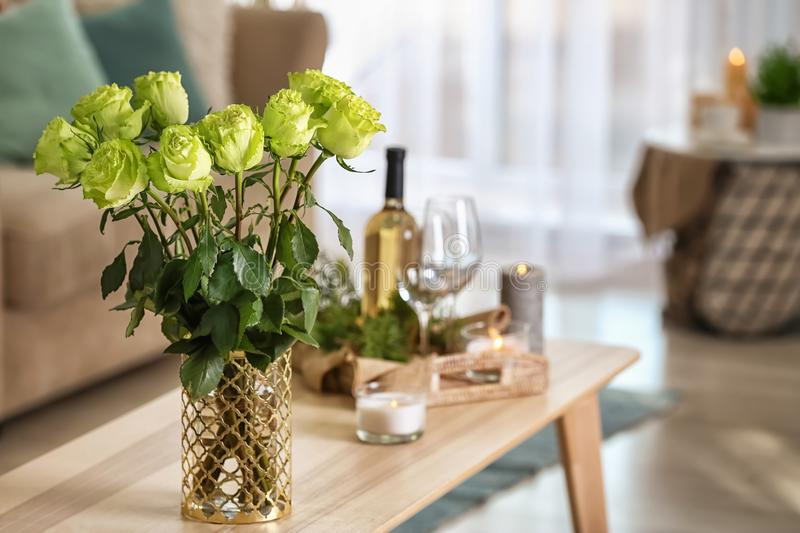 Vase with beautiful green roses on wooden table in room stock photography