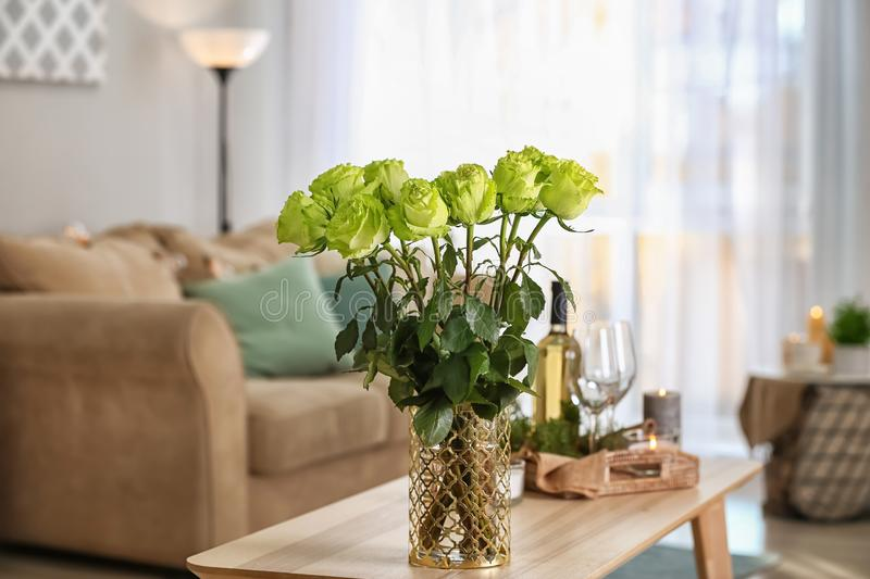Vase with beautiful green roses on wooden table in room stock images