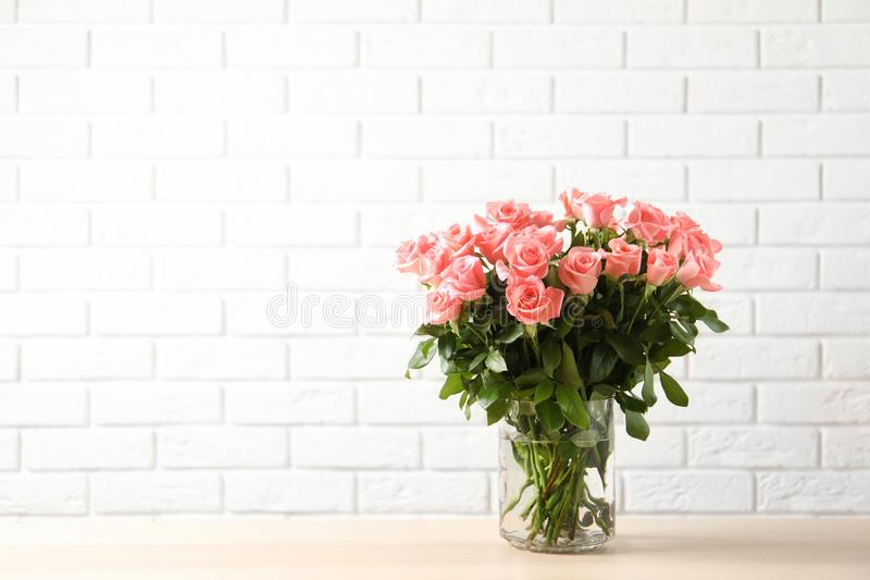 Vase with beautiful rose flowers on table stock photography