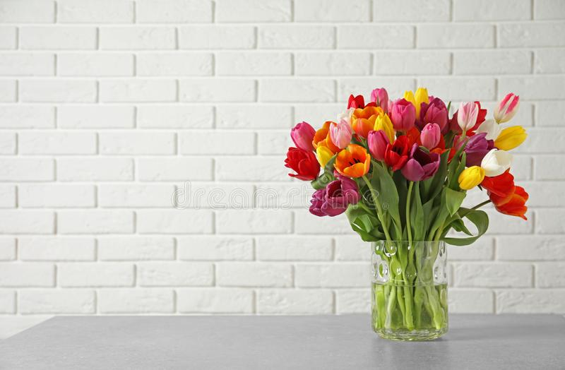Vase with beautiful spring tulip flowers on table near brick wall. royalty free stock photography