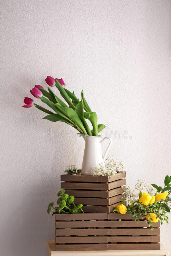 Vase with beautiful tulips and other flowers on wooden boxes royalty free stock photography