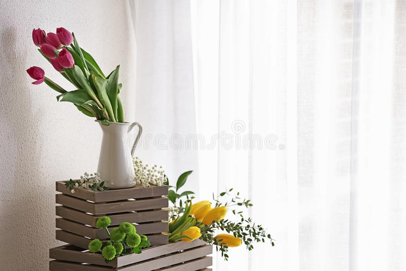 Vase with beautiful tulips and other flowers on wooden boxes royalty free stock photo