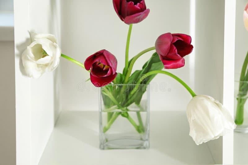 Vase with beautiful tulips on shelf royalty free stock photo