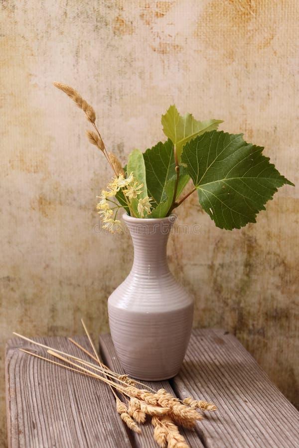 Vase blanc avec un bouquet des fleurs et des feuilles jaunes parfumées des hérissons de tilleul et d'herbe sèche image libre de droits