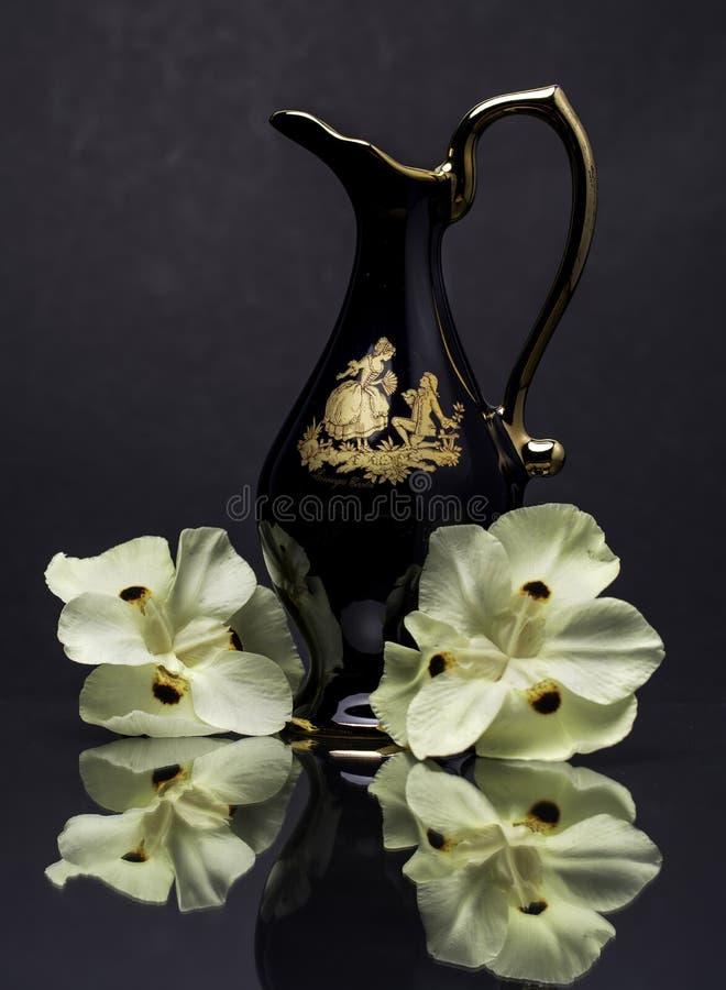 Vase ? carafe de broc de bleu de cobalt avec la fleur et le Grey Background jaunes photos stock