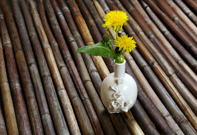 Vase with dandelions. On a table made of cane. background, texture royalty free stock photos