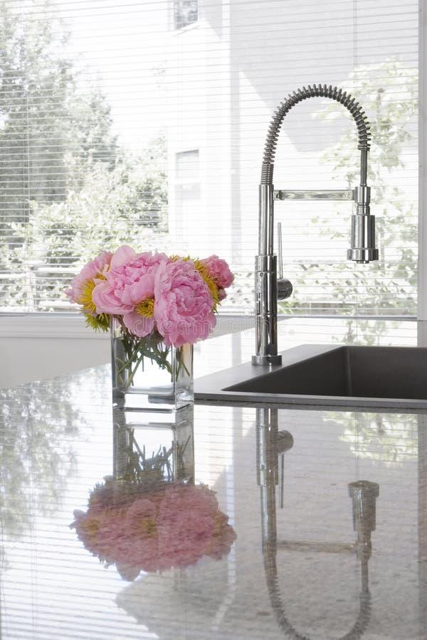 Vase de pivoines sur le bassin de la cuisine moderne images stock