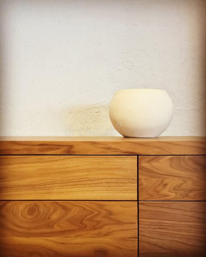 Vase en céramique blanc sur un coffre des tiroirs en bois images libres de droits