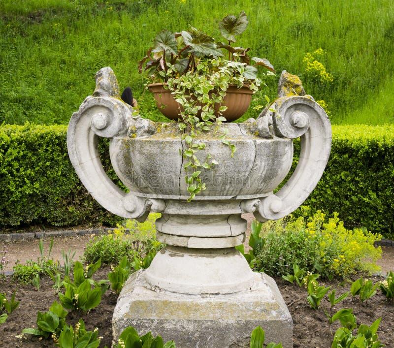 Vase en pierre avec des fleurs photos stock