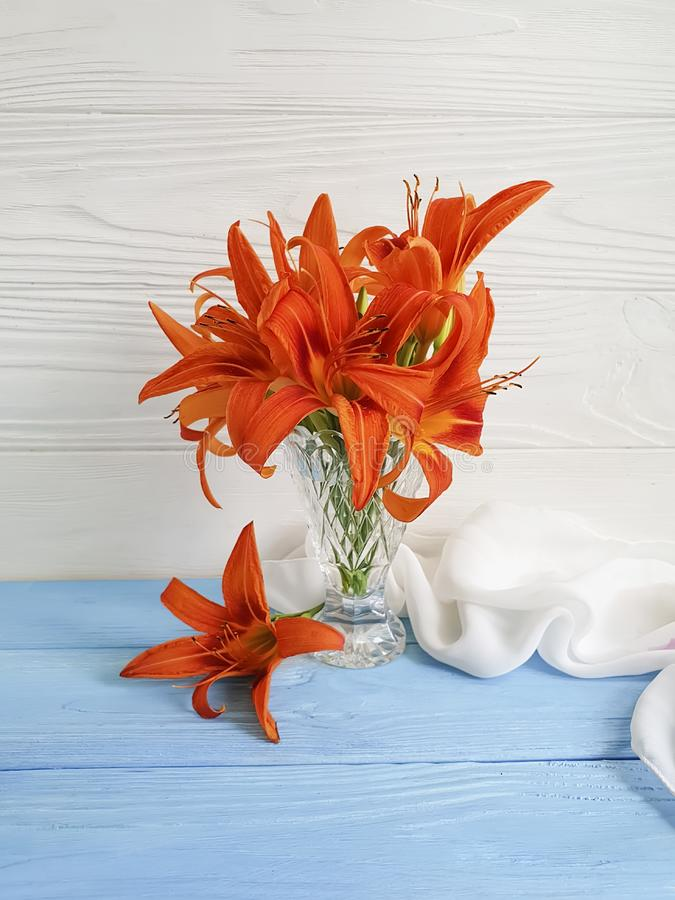 Vase flower lily on a wooden background romantic. Vase flower lily orange on a wooden background romantic royalty free stock photos
