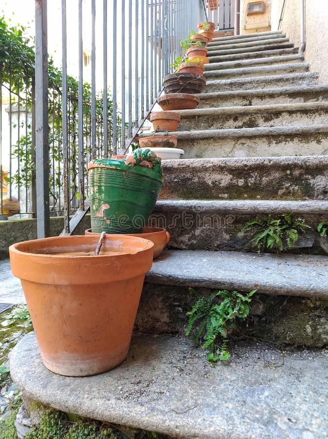 Vase of flower on a stone staircase in an old Italian house. Vases, pot, decoration, background, stairs, steps, railing stock photos