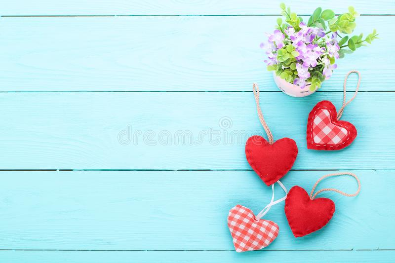 Vase of flowers and hearts on blue wooden background with copy s royalty free stock image