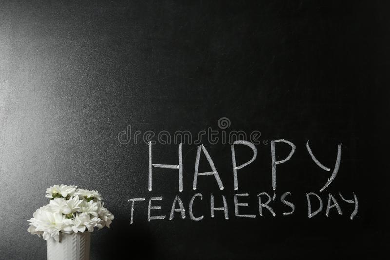 Vase of flowers near blackboard with  HAPPY TEACHER`S DAY, space for text royalty free stock photos