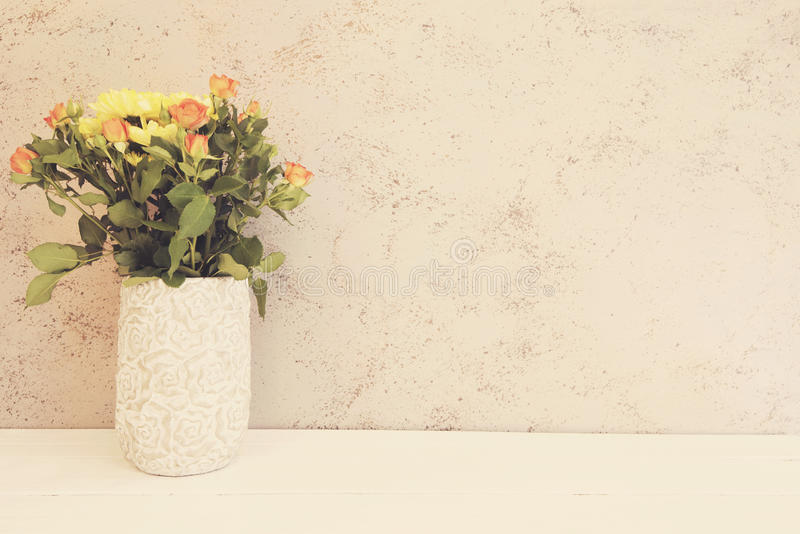 Vase of flowers. Rustic vase with orange roses and yellow chrysanthemums. White background, empty place, copy space. Vintage tinte royalty free stock image