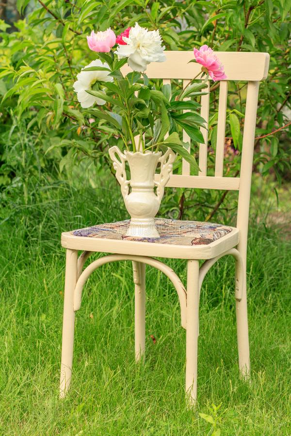 Vase of flowers on a white chair in the garden royalty free stock images