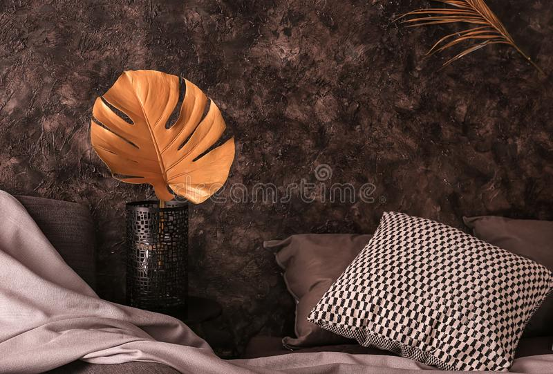 Vase with golden tropical leaf in interior of modern comfortable bedroom stock photos