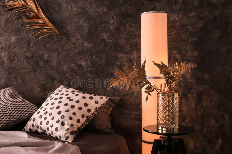 Vase with golden tropical leaves in interior of modern comfortable bedroom stock image