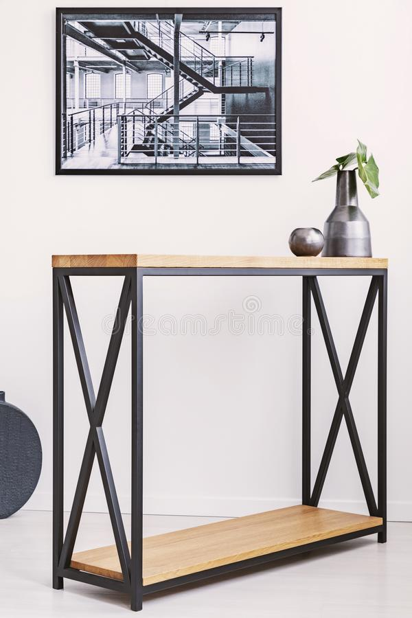 Vase with leaf and candle standing on stylish modern table with metal legs. Industrial poster on the wall stock image