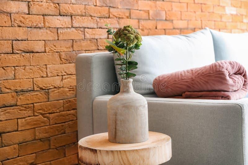 Vase mit Anlagen auf Tabelle im Innenraum des Wohnzimmers lizenzfreie stockfotos