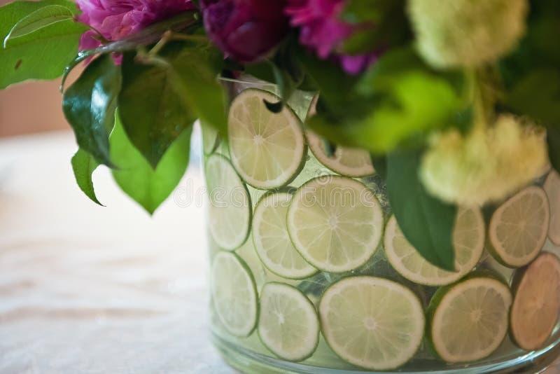 Vase mit Kalk und Blumen gegen eine weiße Tischdecke lizenzfreie stockfotos