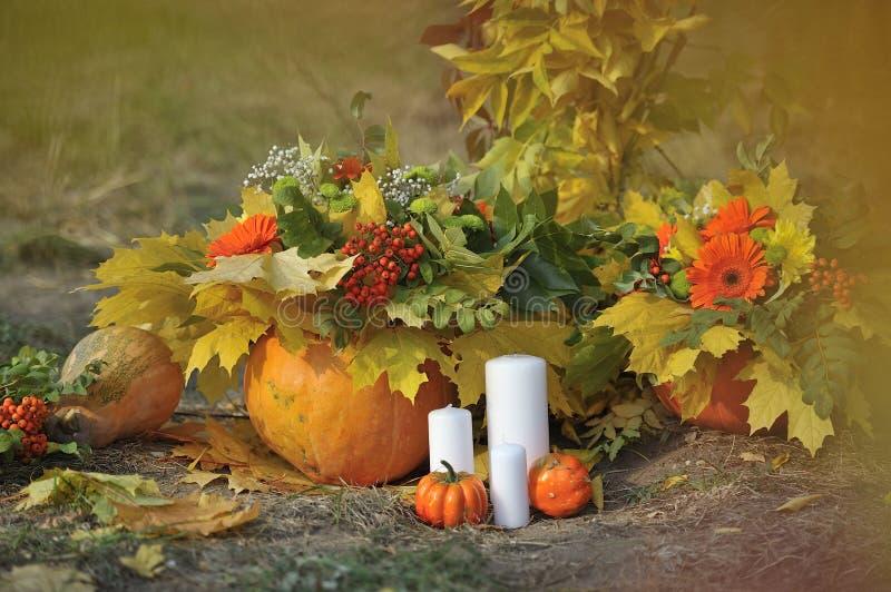 Vase mit trockenen Blättern, Apfel und Kerzen auf dem Rausschmiß lizenzfreies stockbild
