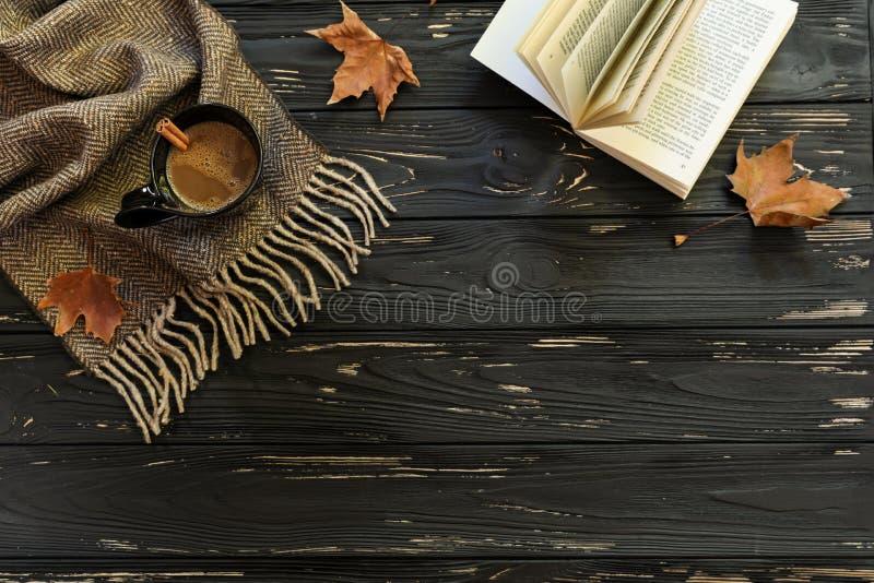 Vase mit trockenen Blättern, Apfel und Kerzen auf dem Rausschmiß Tasse Kaffee, Schal, offenes Buch, Ahornblätter auf schwarzem hö stockbild