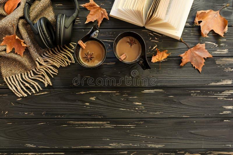 Vase mit trockenen Blättern, Apfel und Kerzen auf dem Rausschmiß Zwei Tasse Kaffees, Zucker, Schal, Kopfhörer, offenes Buch, Ahor stockfotos
