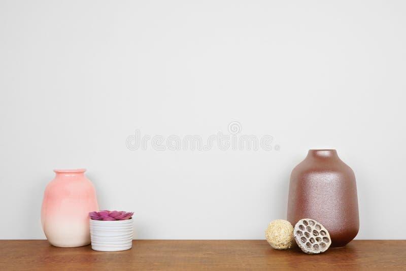 Vase och sukulor från en fabrik på en trähylla mot en vit vägg med kopieringsutrymme royaltyfri foto