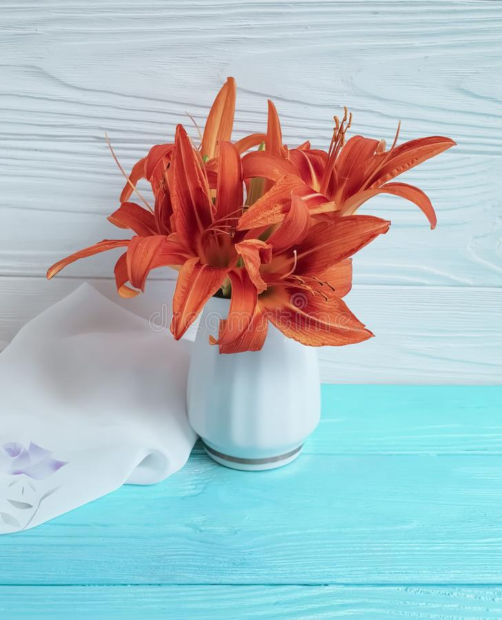 Vase orange lily congratulation on a wooden background textiles. Vase orange lily on a wooden background textiles shawl congratulation stock photography
