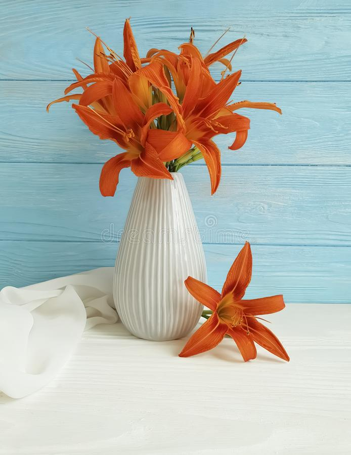 Vase orange lily retro bouquet holiday blooming composition design on a wooden background textiles. Vase orange lily on a wooden background textiles shawl retro stock images