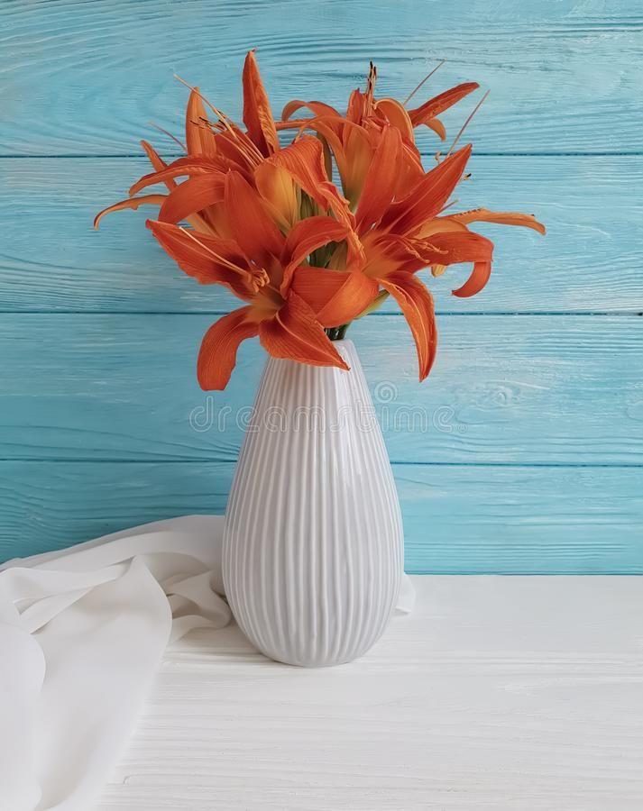 Vase orange lily retro bouquet holiday blooming design on a wooden background textiles. Vase orange lily on a wooden background textiles shawl retro holiday royalty free stock photo
