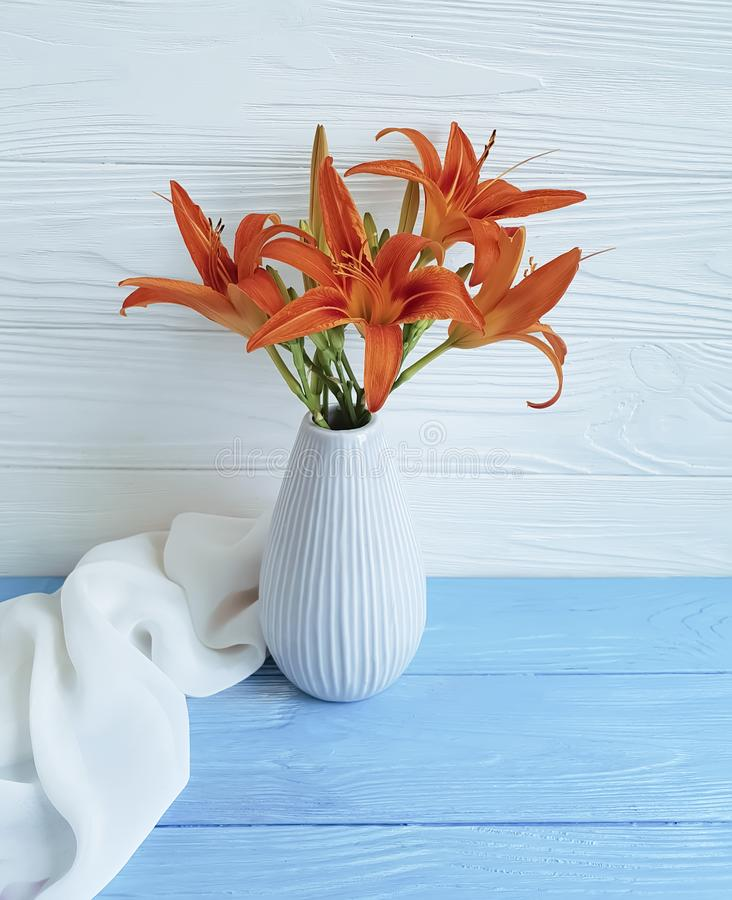 Vase orange lily retro table bouquet holiday blooming composition design on a wooden background textiles. Vase orange lily on a wooden background textiles shawl royalty free stock photo