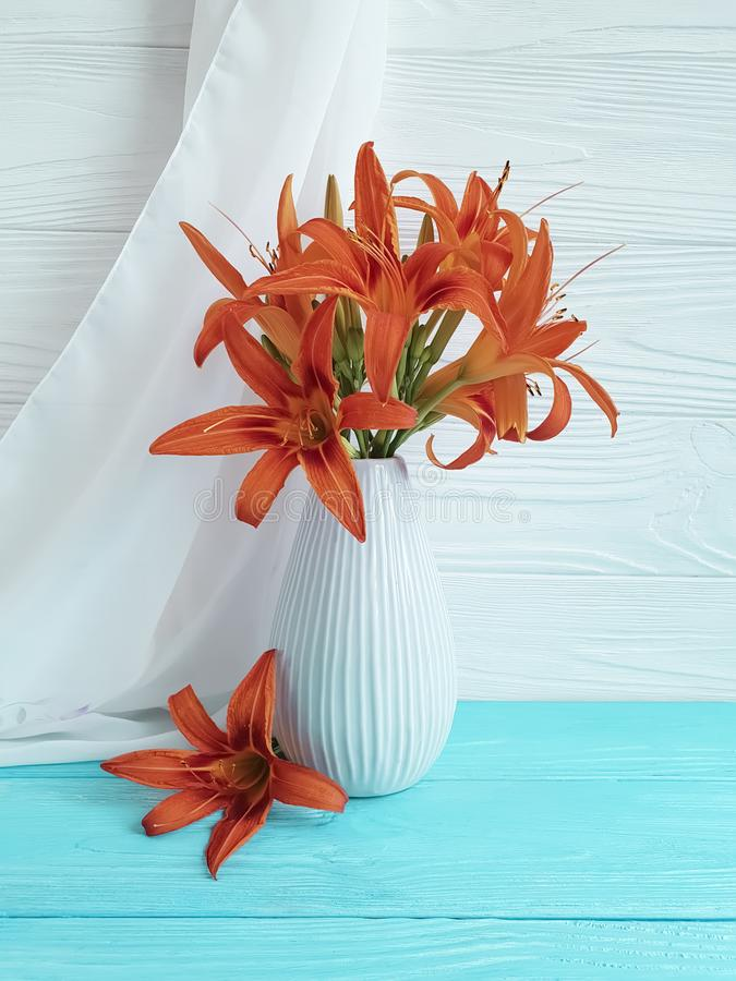 Vase orange lily retro holiday composition on a wooden background textiles. Vase orange lily on a wooden background textiles shawl retro holiday nostalgia royalty free stock image