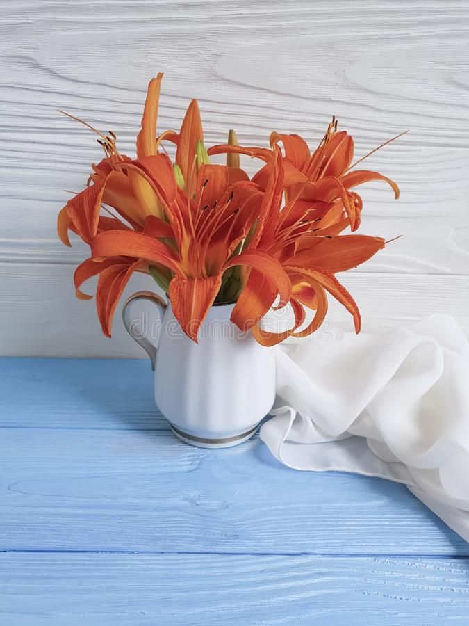 Vase orange lily on a wooden background textiles. Shawl royalty free stock image