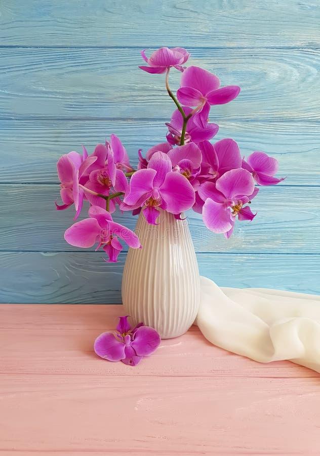 Vase orchid flower arrangement shawl color bouquet freshness modern decorate elegance arrangement on a wooden background stock photo