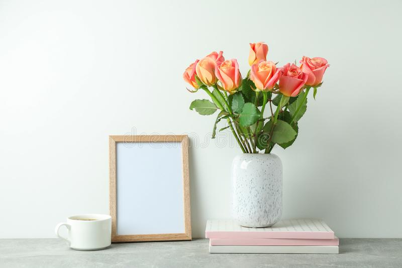 Vase with pink roses, copybooks, empty frame, cup of coffee on grey table royalty free stock photos
