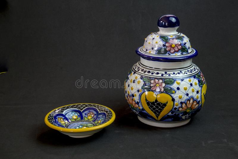 Vase with plate made of Talavera. Elegance is the name of Talavera family of cute little vase and plate on a black background royalty free stock image